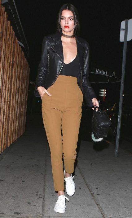 Kendall Jenner usando un pantalón caqui y una blusa negra con escote