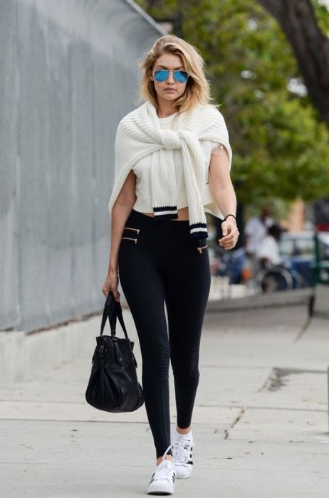 Gigi Hadid goes for a sport look with zipper moto leggings by Blue Life Fit, a white crop top, tennis shoes, and a knit sweater loosely tied around her shoulder.: