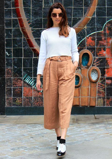 Chica usando usando pantalones anchos y cortos color camel