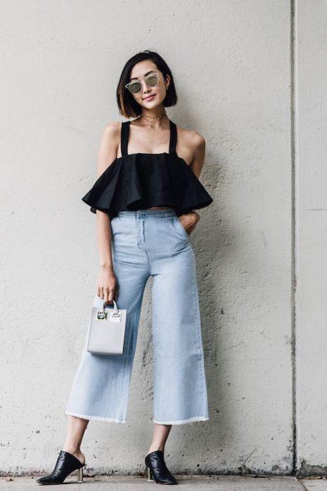 Chica usando usando pantalones anchos y cortos estilo jeab con un top de holanes
