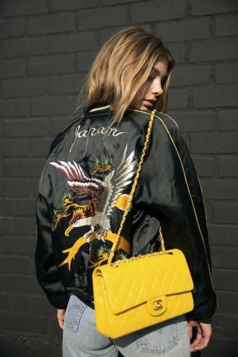Chica usando una bolsa amarilla de chanel sobre una bomber jacket