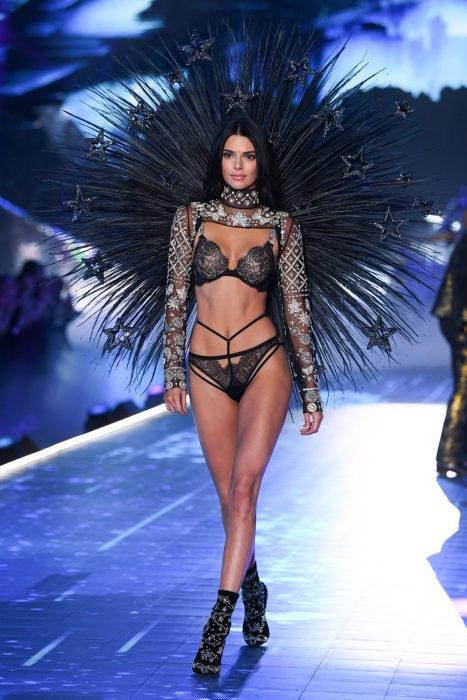 Kendall jenner caminando durante el desfile de victoria's secret usando unas plumas y lencería negra