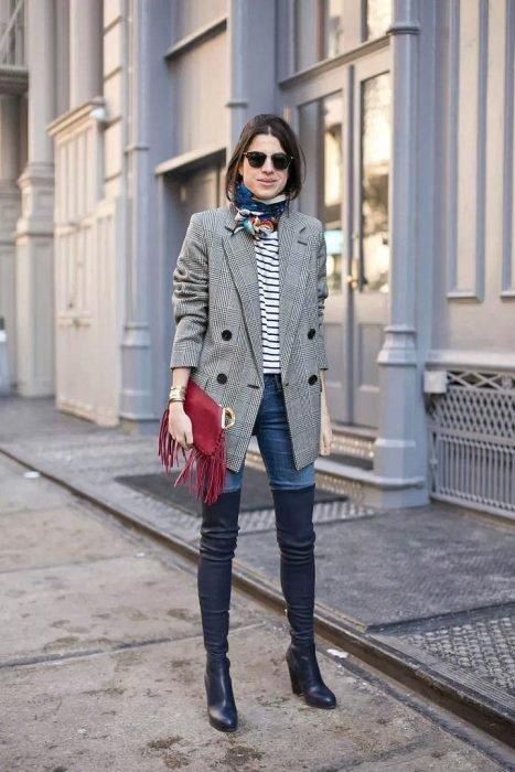 Chica usando un sueter cuadrado, jeans y botas largas