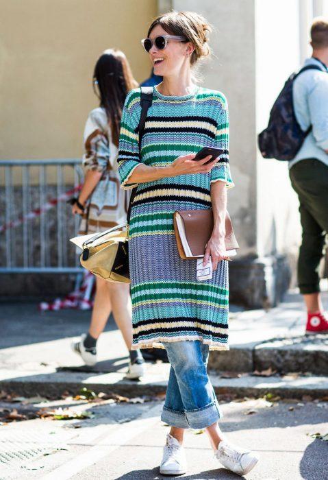 Chica con vestido para el frío y pantalón de mezclilla