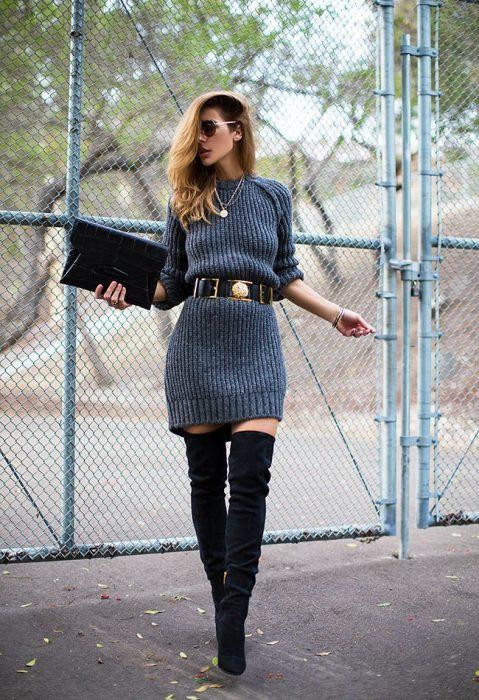 Chica con vestido gris de invierno y botas largas