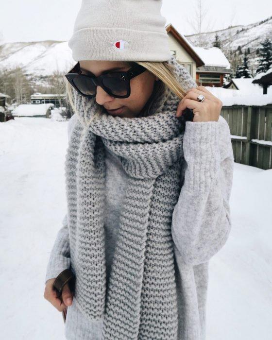 Chica usando una bufanda de color gris y un gorro blanco