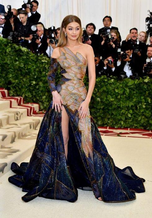 mujer rubia con vestido azul con dorado