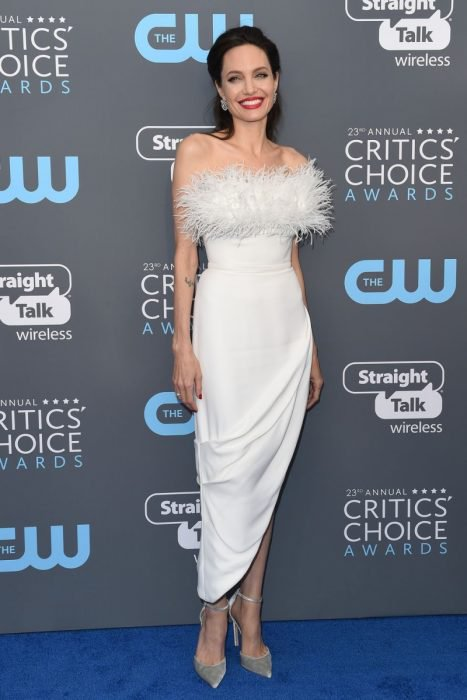 mujer blanca con cabello negro y vestido blanco con pulmas