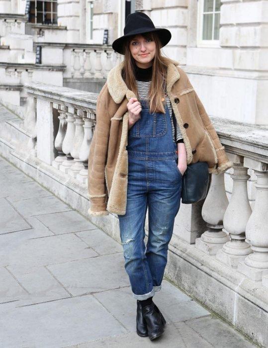 Chica usando un overol con botines y sombrero