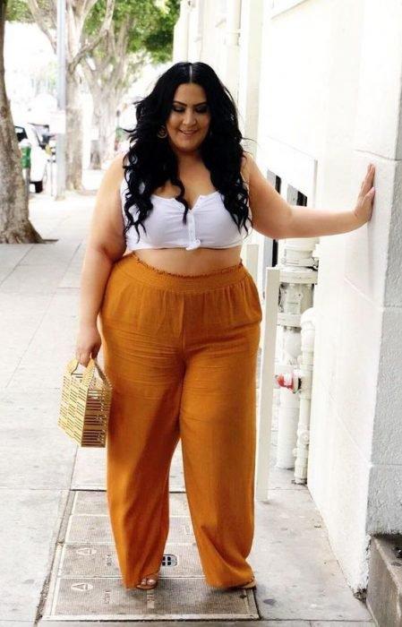 mujer con pantalón naranja de crop top blanco