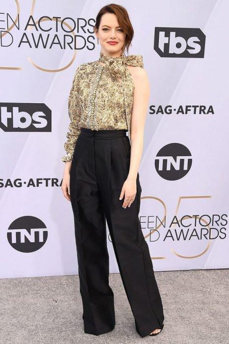 Emma Stone en los SAG Awards 2019 con una blusa doradoa y un pantalón negro es considerada una de las mejores vestidas
