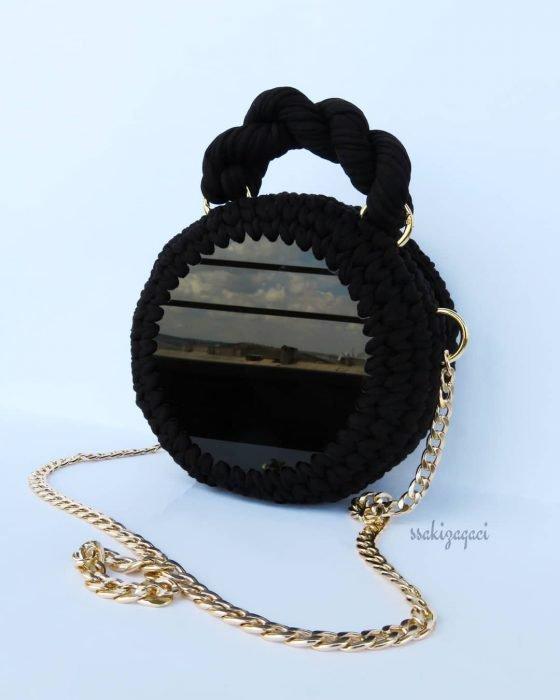 bolso negro circular con cadena dorada