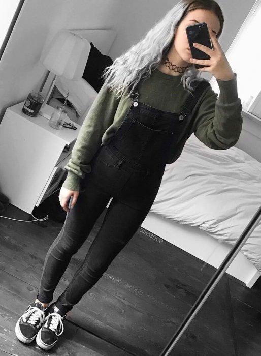 Chica de cabello gris con overol negro, suéter verde y chocker