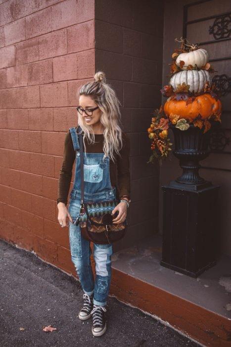 Chica rubia con overol de mezclilla y bolsa bohemia