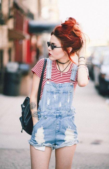 Chica de cabello rojo con overol corto y camisa a rayas blancas y rojas