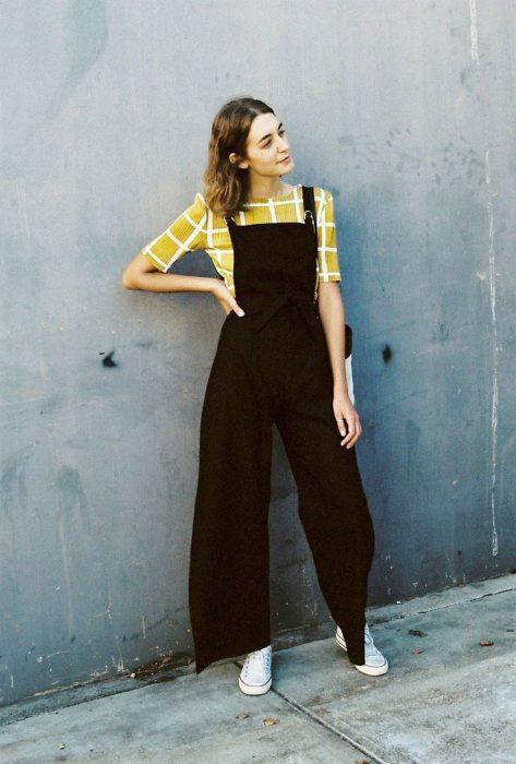 Chica retro con overol ancho y blusa amarilla sonriendo con la mano en la cintura