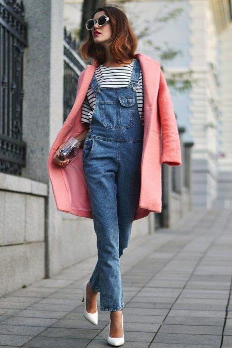 Chica con overol de mezvlilla, playera a rayas, saco rosa y lentes de sol