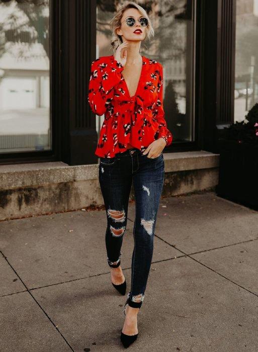 Chica con blusa roja, jeans desgastados y tacones
