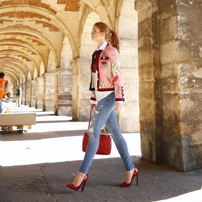 Chica pelirroja con saco, pantalón de mezclilla y tacones