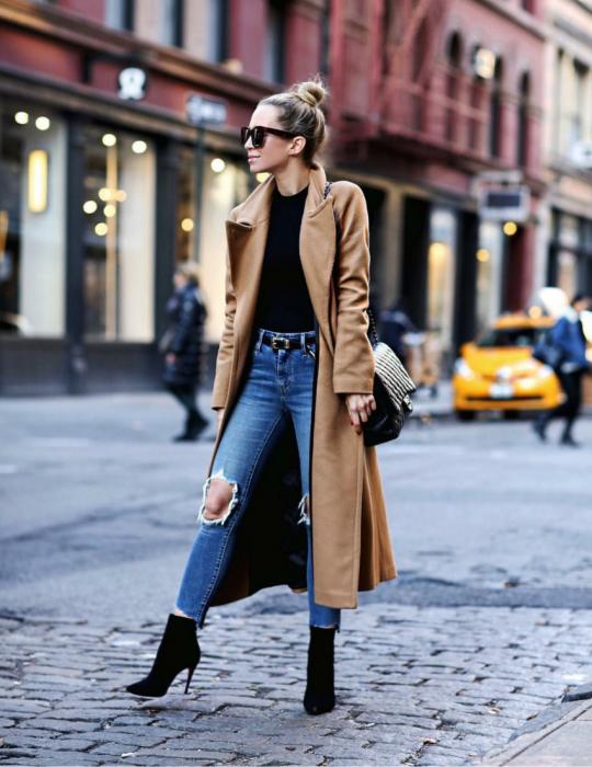 Mujer en la calle usando gabardina, jeans y tacones