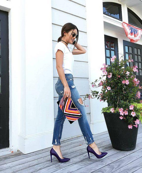Chica castaña con blusa blanca, jeans y zapatos morados de tacón