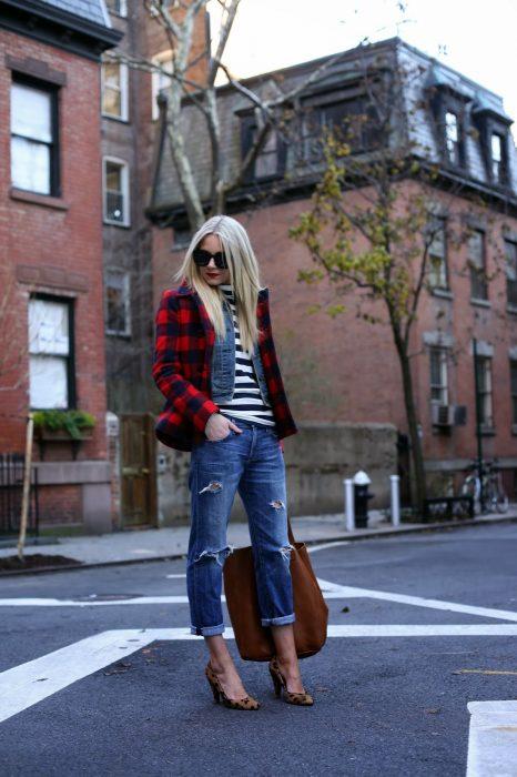 Chica rubia con abrigo de cuadros, con camisa de rayas, pantalón de mezclilla, tacones de animal print en la calle