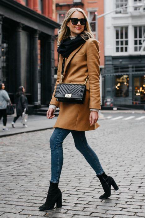 Chica rubia con saco beige, pantalones de mezclilla y tacones columna caminando en la calle