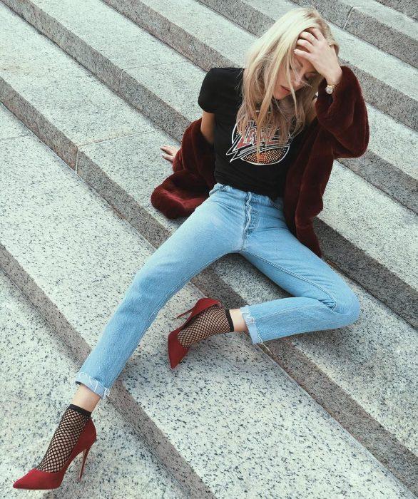 Chica rubia con blusa rockera, abrigo rojo vino afelpado, jeans y tacones rojos con medias de red