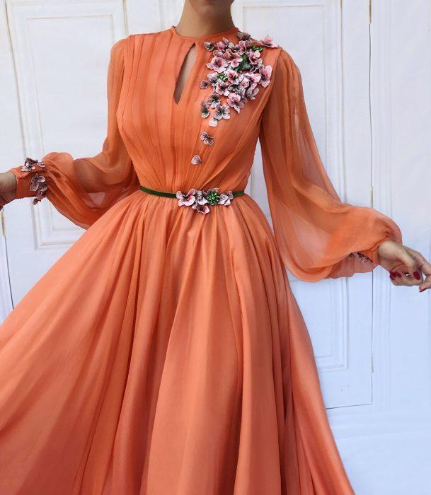 Vestido en corte A, color anaranjado melón adornado con flores rosas