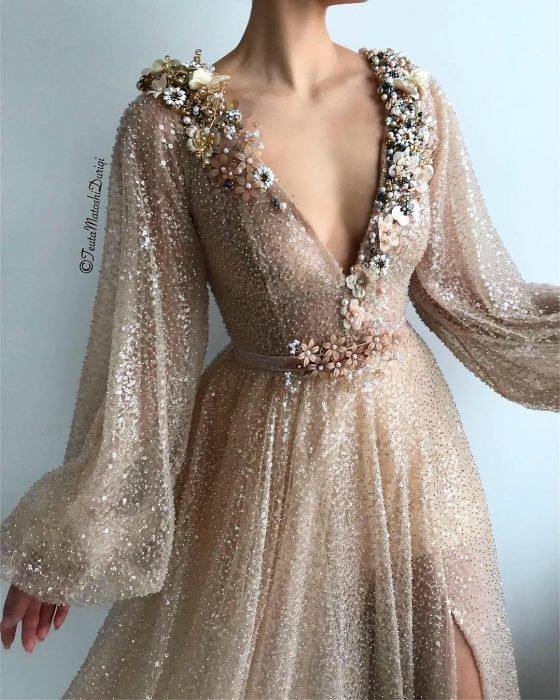 Vestido en corte A, color champagne adornado con brillos y flores