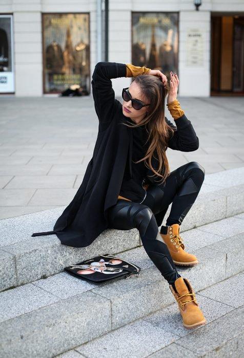 Chica sentada en escaleras peinando su cabello, trae unos leggins negros, blusa negra y suéter negro. Además de botas militares cafés y gafas en el rostro