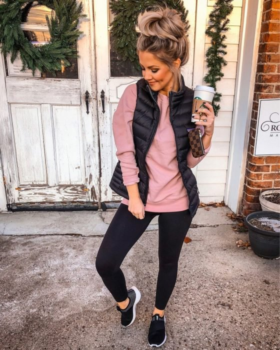 Chica posando enfrente de una puerta de madera blanca rustica, con leggins negro, suéter rosa con chaleco azul. De calzado lleva tenis negros y en su mano un café caliente