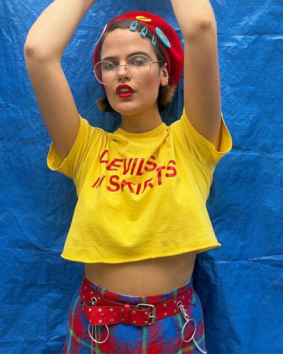 Chica luciendo una camiseta amarilla, pantalón de cuadros, un sombrero rojo y broches azules