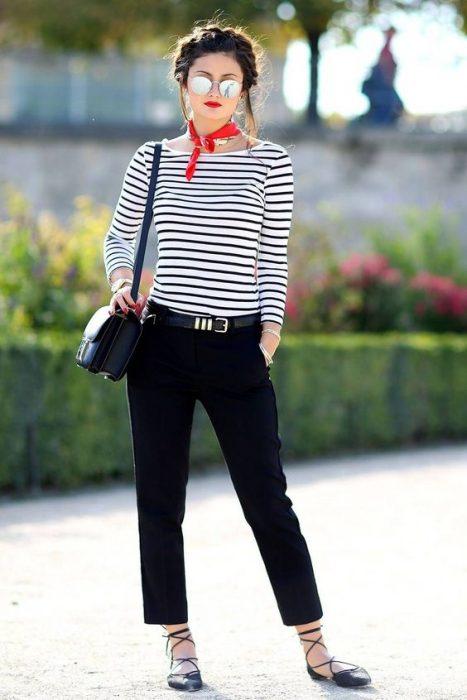 Chica con cabello recogido con trenza, blusa estilo nay y pantalón azul marino en la calle