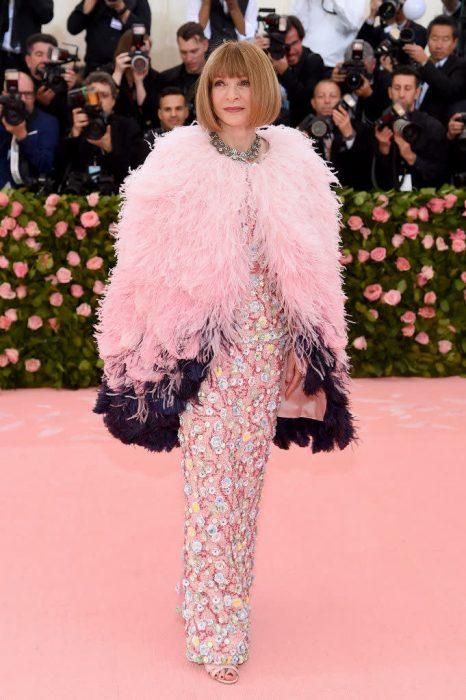Anna Wintour, editora de Vogue Us, en la gala del MET usando un vestido rosa de lentejuelas con una capa de plumas en color rosa y morado