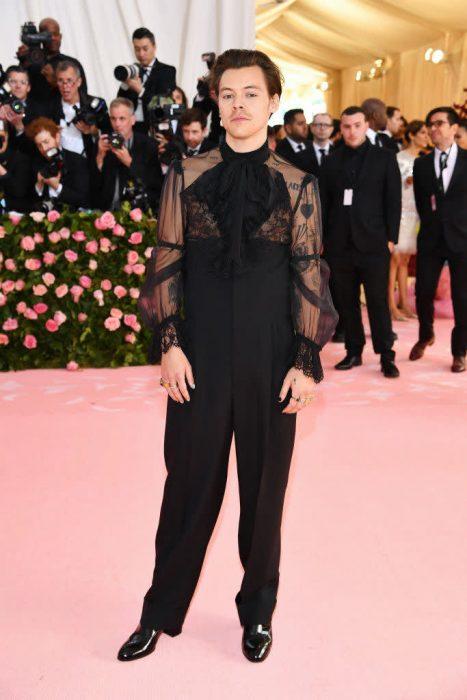 Harry Style usando un atuendo en color negro con transparencias y aretes de perlas durante la Gala MET de Nueva York