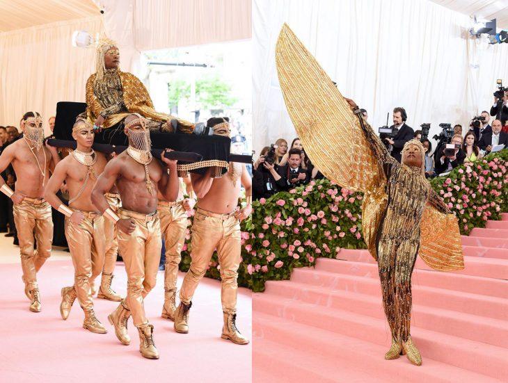 Billy Porter entrando a la Gala Met siendo cargado por varios hombres y después mostrando su atuendo que consiste en representar a un dios egipcio