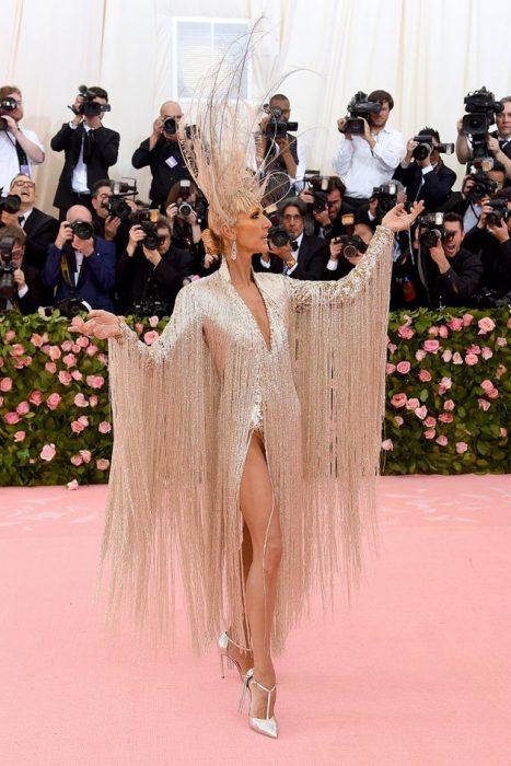 Celine Dion usando un vestido dorado con piedras y un recogido bajo con un tocado de plumas mientras posa para los fotógrafos del Met Gala