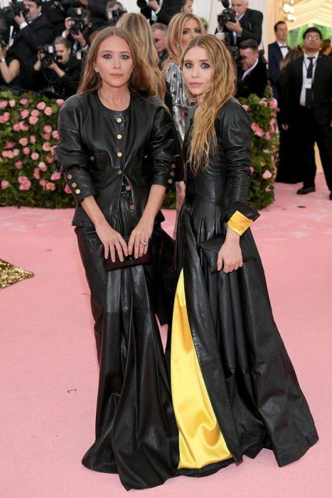 Mary-Kate y Ashley Olsen usando vestidos similares de cuero negro con aplicaciones en amarillo durante la Gala del MET
