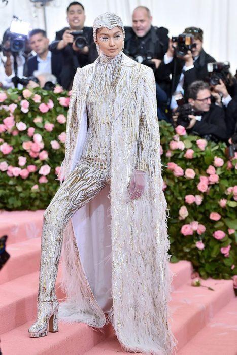 Gigi Hadid usando un traje de color blanco con estampado dorado, botas del mismo color y un abrigo largo. En la cabeza usa una capucha de color plateado con aplicaciones en pedrería