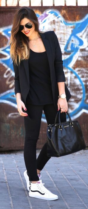 Chica usando un outfit negro con tenis de color blanco marca Vans