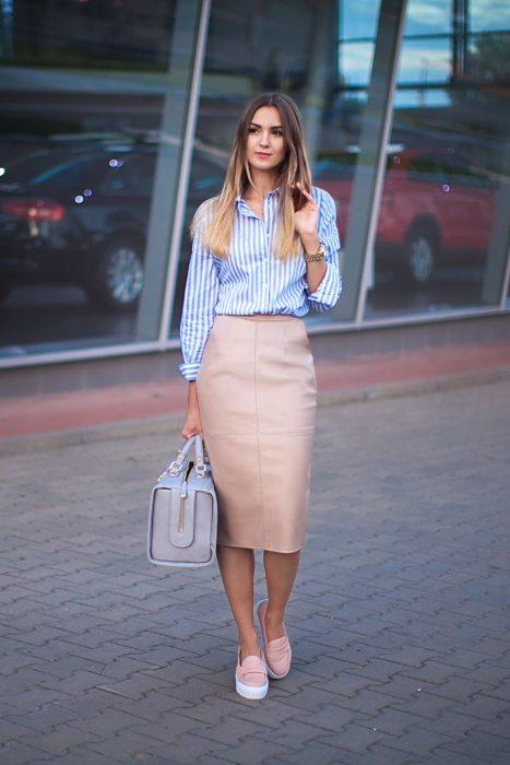 Chica parada en la calle usando un outfit de falda de lápiz color rosa, blusa de líneas en color azul y zapatos color rosa