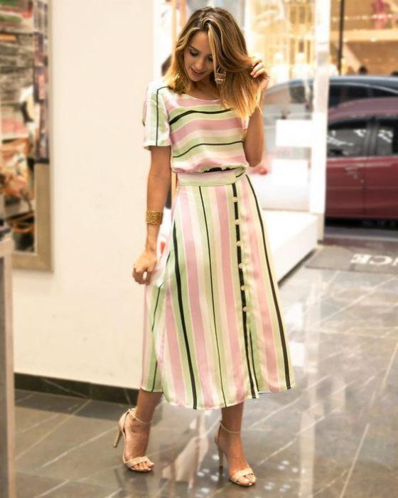 Chica usando un vestido midi de color blanco con líneas de color verde con rosa mientras posa para una foto