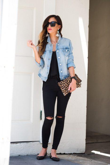 Chica usando una chaqueta de mezclilla sobre un outfit negro mientras posa para una fotografía