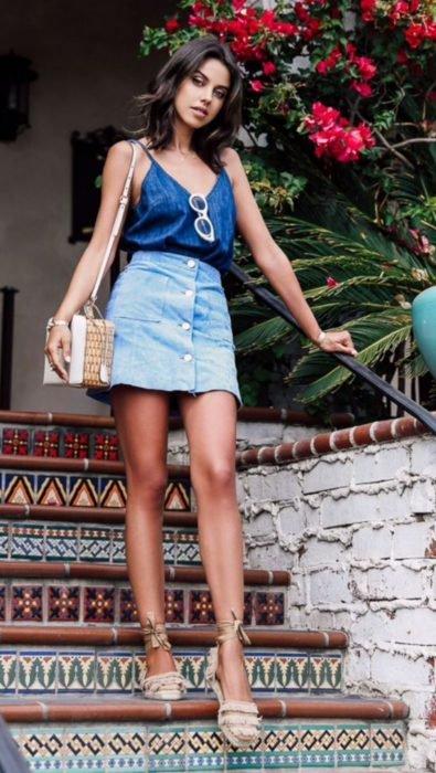 Chica posando para una foto mientras está parada en unas escaleras usando un outfit de mezclilla y alpargatas de color beige