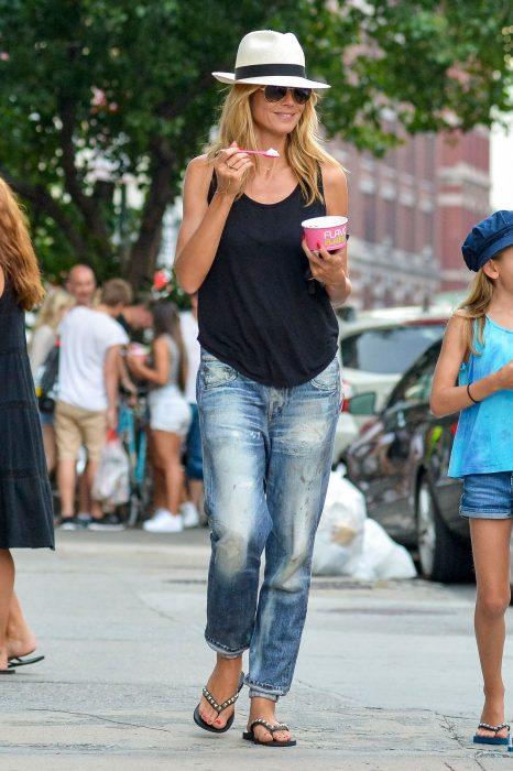 Chica caminando por la calle comiendo helado mientras usa jeans, una blusa negra, sandalias y sombrero