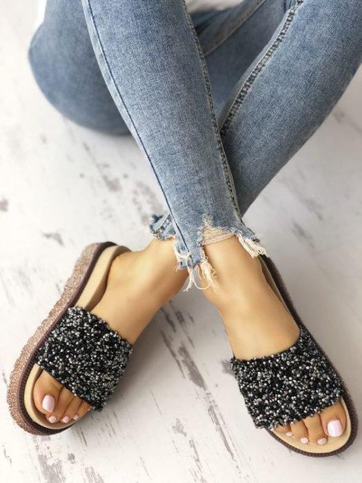 Pies de una chica usando jeans y unas sandalias de color negro con brillos