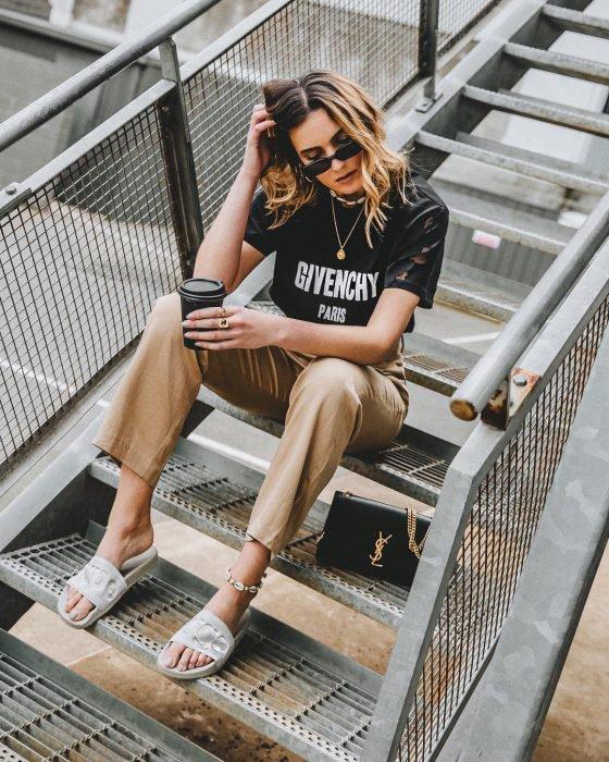 Chica usando unas sandalias de color blanco, pantalón café y blusa negra mientras está sentada en unas escaleras tomando café