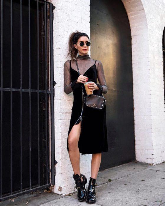 Chica usando un vestido de terciopelo con botas y lentes