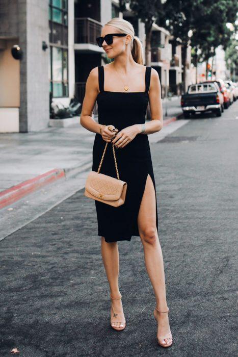 Chica parada en medio de la calle usando un vestido con abertura hasta la rodilla, lentes de sol y cartera de color nude